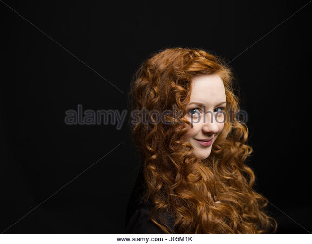 Portrait smiling woman with long curly red hair against black background - Stock Image