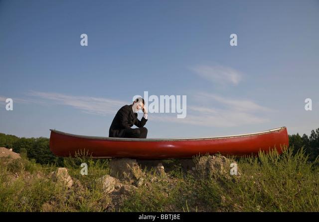 Business man stranded in canoe - Stock Image