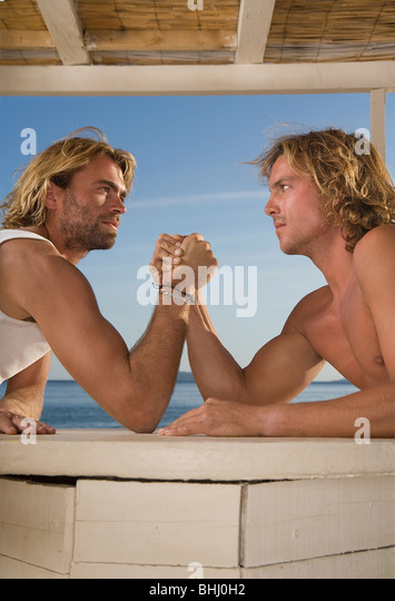 young men arm wrestle at beach - Stock Image