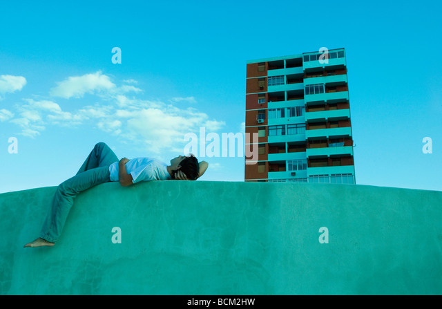 Young man lying on ledge, looking at sky, high rise apartment building in background - Stock Image