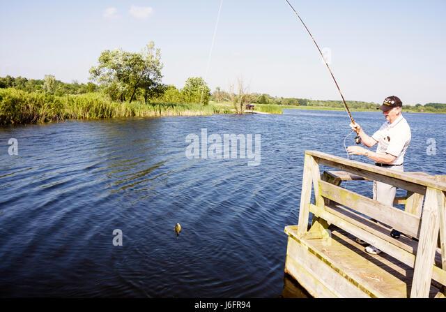 Wisconsin Kenosha Kansasville Richard Bong State Recreation Area Wolf Lake Fishing Pier man senior angler water - Stock Image