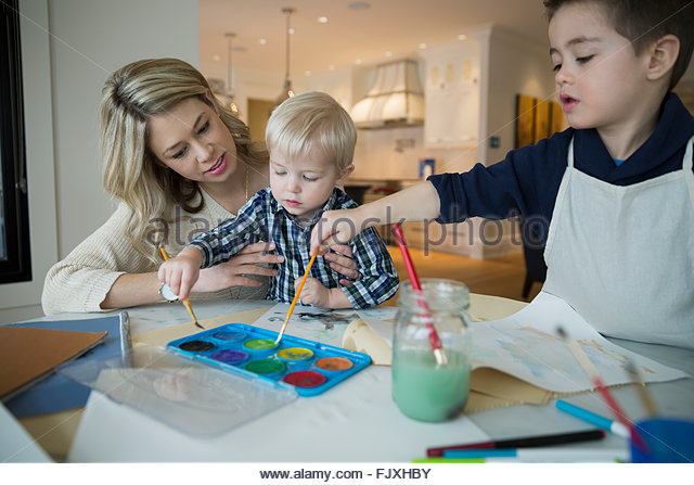 Mother and sons watercolor painting at table - Stock Image