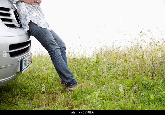 detail of young woman leaning against car - Stock Image
