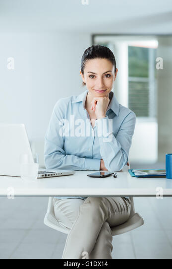 Beautiful confident female manager sitting at office desk and smiling at camera with hand on chin, room interior - Stock Image