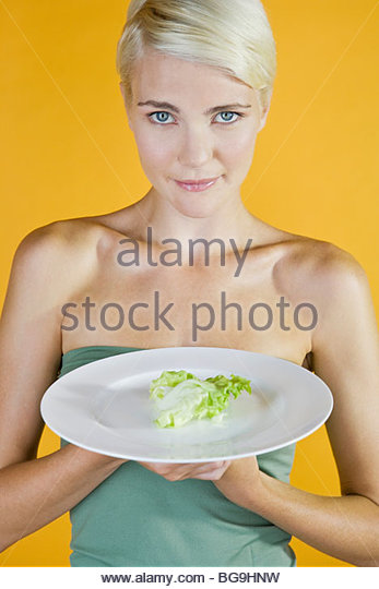 A Young Woman With A Piece Of Lettuce On A Plate - Stock Image