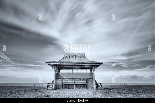 A small shelter set against an artistically blurred sky on Blackpool seafront (monochrome fine art) - Stock-Bilder