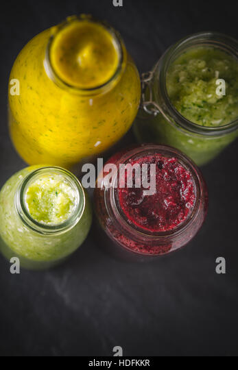 Bottles and jar with different smoothie on the dark stone table vertical - Stock Image