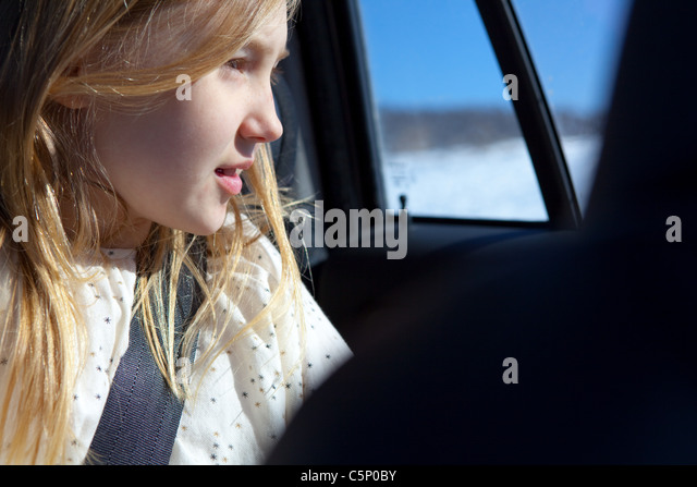 Young girl looking through car window - Stock Image
