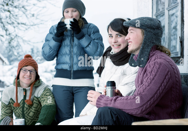 Group of young people drinking warm tea - Stock Image