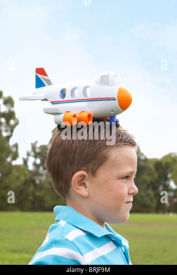 boy with plastic airplane on his head - Stock Image