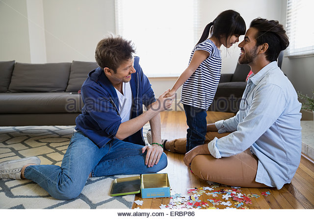 Homosexual couple and daughter assembling jigsaw puzzle - Stock Image