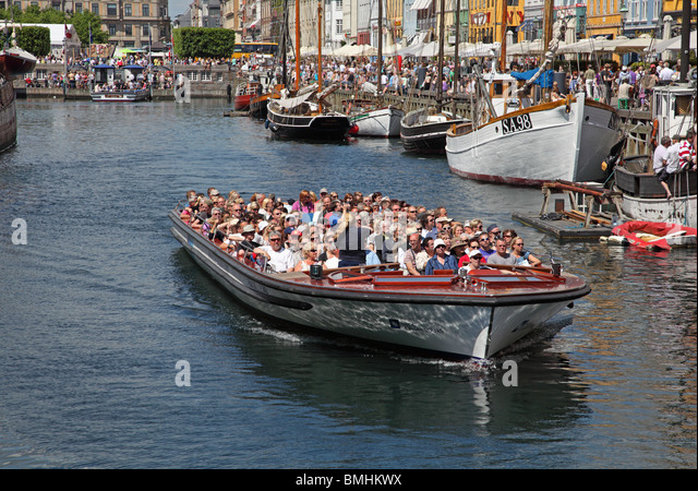 A canal tour cruise boat full of summer tourists leaving Nyhavn on a sightseeing cruise in the port of Copenhagen - Stock Image