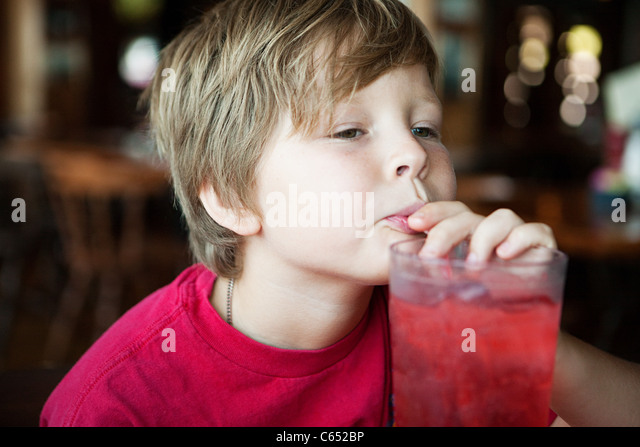 Boy drinking red soft drink - Stock Image