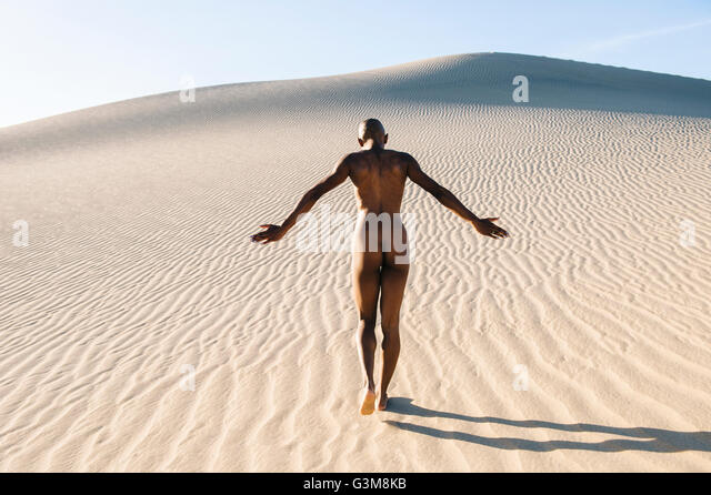 Rear view of nude woman in desert - Stock Image