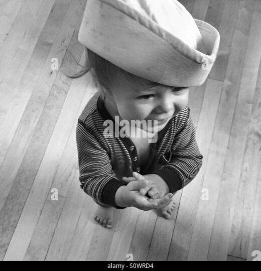 Happy baby wearing a sailor's hat, in black and white - Stock Image