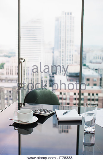 Desk with coffee, calculator, notepad and water - Stock Image