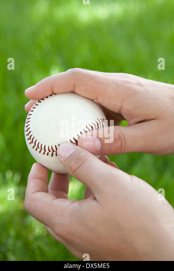 Man's hands holding baseball in grass, close up - Stock Image