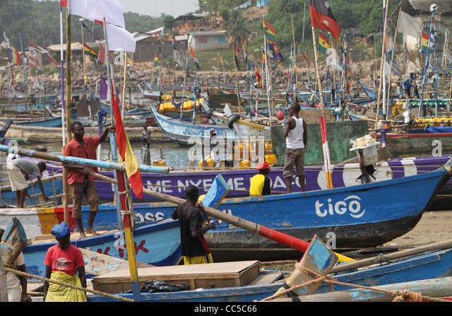 Fishermen preparing fishing boats in harbour on Cape Coast, Ghana - Stock Image