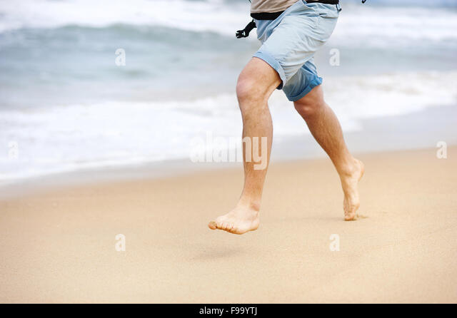 Detail of male feet running at the sandy beach - Stock Image