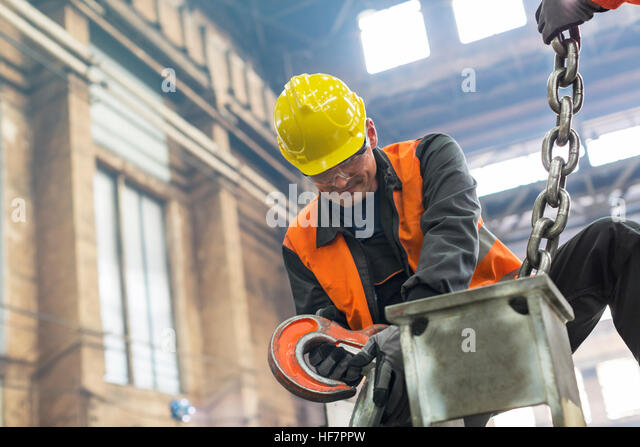 Steel worker fastening crane chain to steel in factory - Stock Image