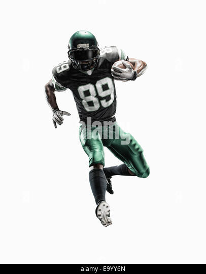 Studio shot of young male football player running with ball - Stock-Bilder