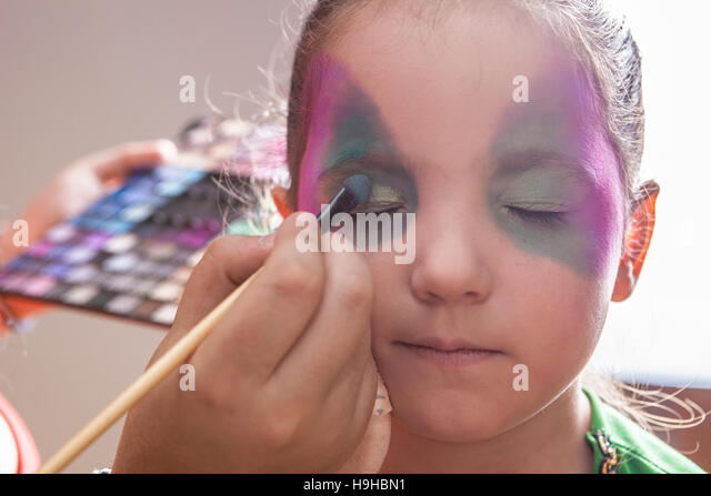 Little cute girl making facepaint before halloween party. The make-up artist is applying some colors while she closes - Stock Image