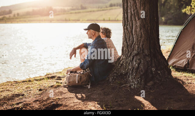 Portrait of middle aged couple sitting under a tree near the lake. Mature couple relaxing at their campsite. - Stock Image