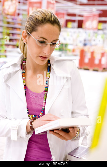 Woman looking at book in supermarket - Stock Image