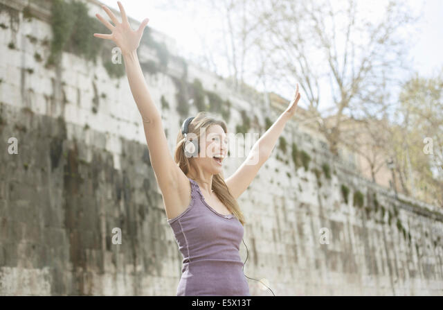 Happy young woman, wearing headphones and raising arms - Stock Image