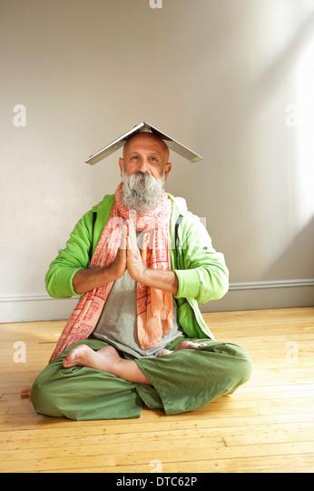 Senior man in lotus position with laptop on head - Stock-Bilder