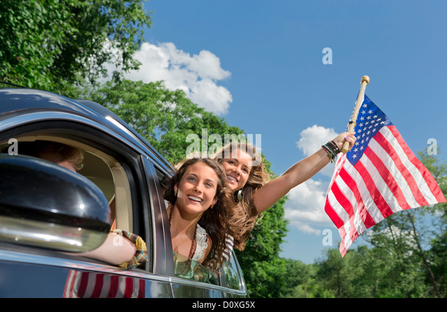 Two friends leaning out of car window holding american flag - Stock Image
