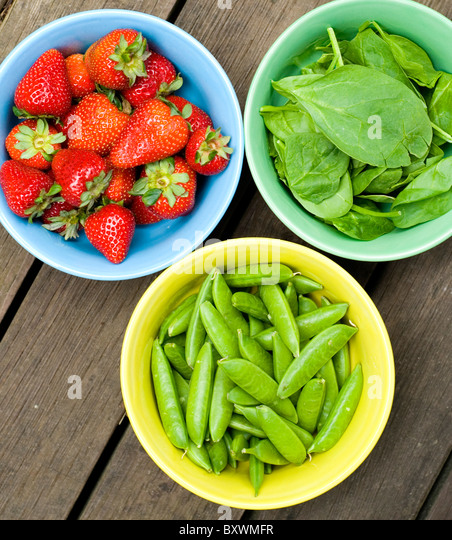 Three bowls, one with strawberries, one with spinach leaves and another with snow peas - Stock Image