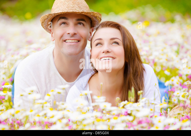 Beautiful young family laying down on wild camomile glade and looking up on sky, having fun in spring park, love - Stock Image