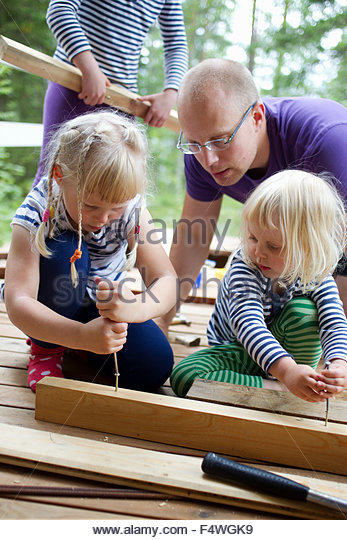 Father and daughters (2-3, 6-7) at summer house - Stock Image