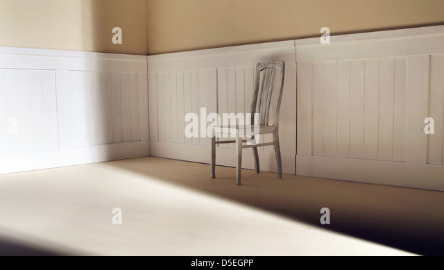 Bright interior with old chair against wall - Stock Image