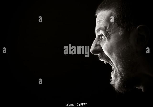 Portrait of screaming angry man on black background - Stock-Bilder