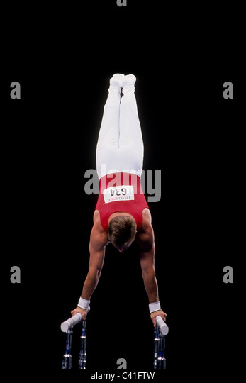 Male gymnast on the parallel bars. - Stock Image