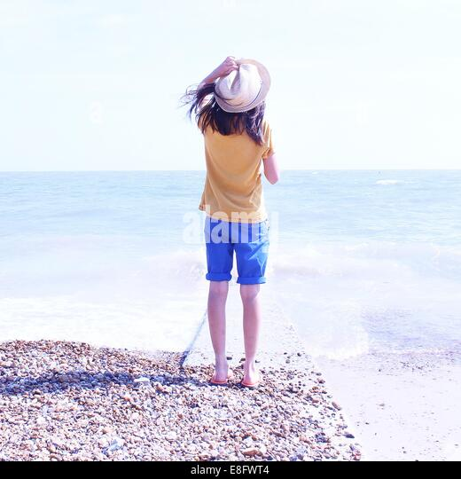 Rear view of girl standing on beach holding hat - Stock Image