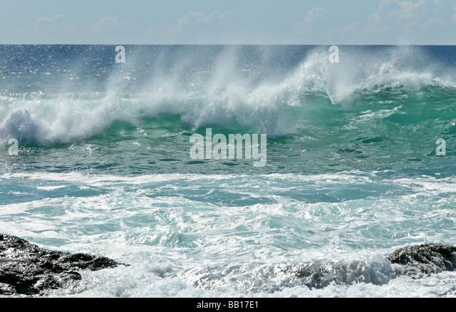 Waves breaking near rocks - Stock Image