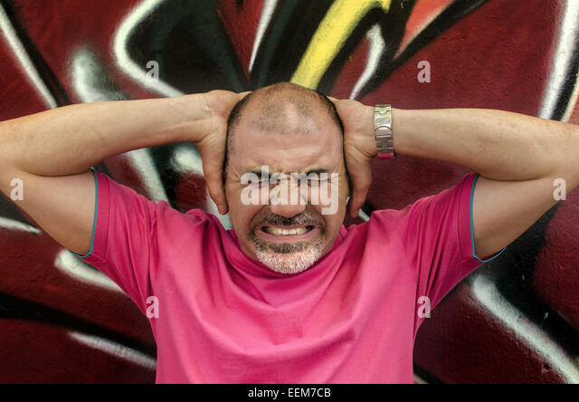 Man frowning and holding head in hands - Stock-Bilder