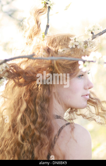 Woman with long hair between flowering branches, portrait - Stock Image