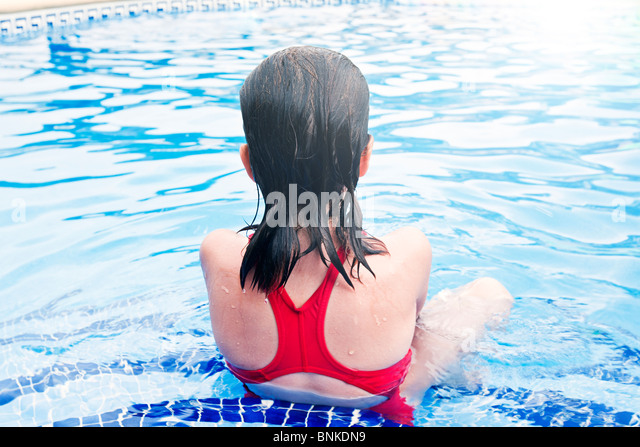 Shot of a Young Child Sitting on Swimming Pool Set, facing away from Camera - Stock Image