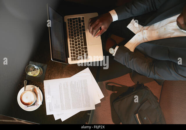 Top view of businessman sitting at coffee shop working on laptop computer. Coffee, water and documents on table. - Stock Image
