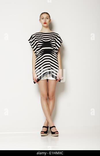 Attitude. Modern Classy Woman in Grey Elegant Clothing. Crossed Legs - Stock-Bilder