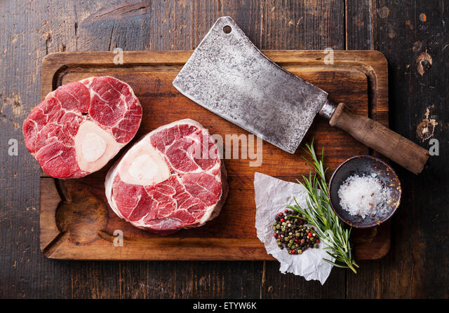 Raw fresh cross cut veal shank and seasonings for making Osso Buco on wooden cutting board with meat cleaver - Stock Image