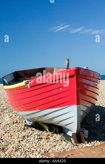 Red and white wooden rowing boat on Brighton beach, UK - Stock Image