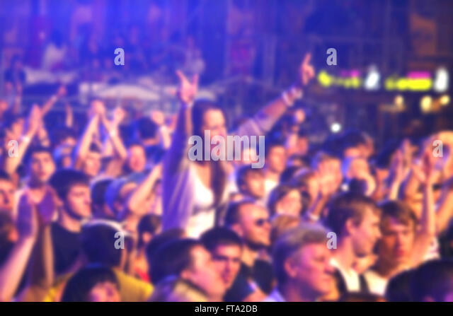 Blurred unrecognizable people dance during rock concert - Stock Image