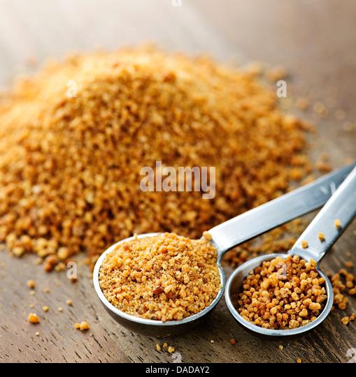 Organic coconut palm sugar in measuring spoons - Stock Image