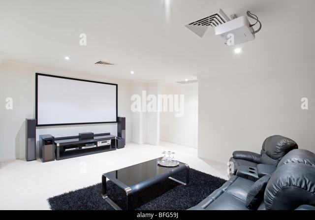 home theater room with black leather recliner chairs, projector in ceiling and projector screen on wall. - Stock-Bilder
