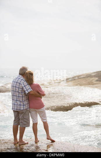 Older couple hugging on beach - Stock-Bilder